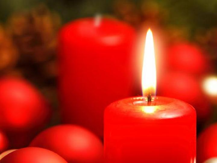 Advent wreath with one lit candle.