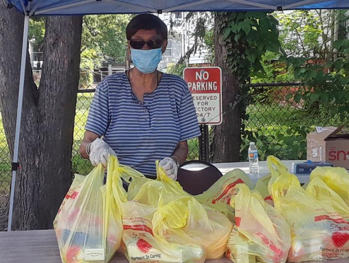 Volunteer Joyce Ifill staffs a table at the Epiphany and Christ Church, Orange food pantry on June 20. GERALDINE STEMPER PHOTO