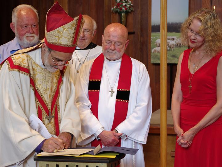 Bishop Mark Beckwith signs the Unification Document