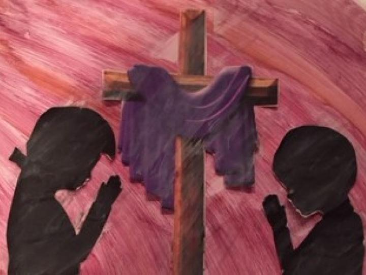 Silhouette of two children praying on either side of a cross draped in purple.