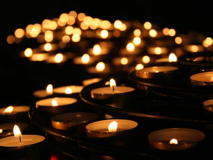lit votives in a darkened room