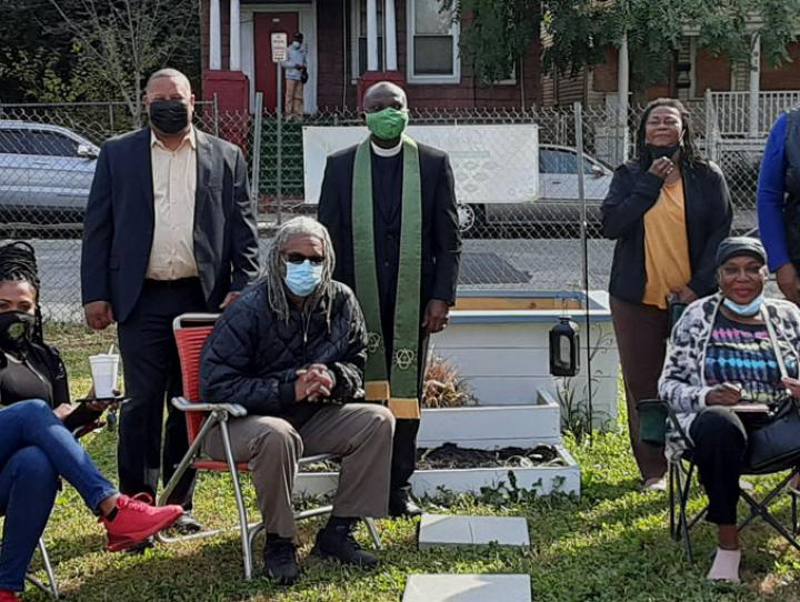 The Rev. Sylvester Ekunwe of St. Andrew's, Newark (center), with Councilman John Sharpe James of Newark's South Ward (on his right) and members of the 17th and 18th Streets Community Association, in one of the empty lots that will be used for a community garden.
