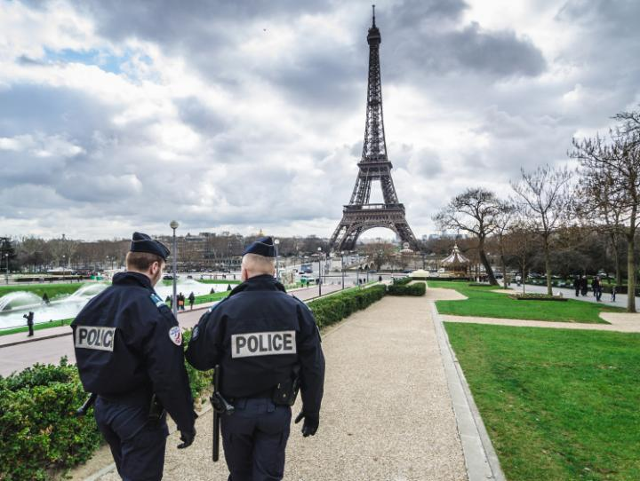 French police patrol the gardens surrounding the Eiffel Tower.