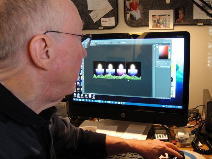 Author John Rollins editing photos for a website.