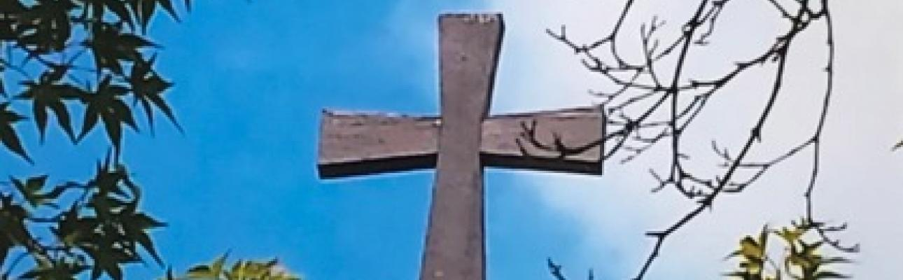 Picture of a cross against a blue morning sky