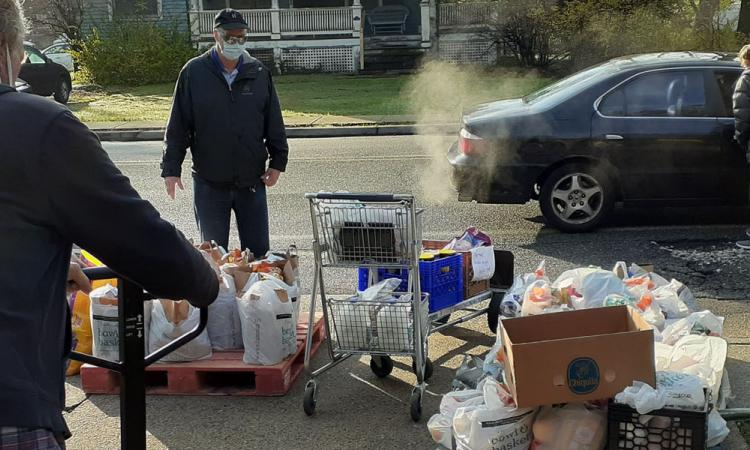 Volunteers distribute bags of food to cars lined up in front of St. Agnes, Little Falls. PHOTO COURTESY BOB DOMBROWSKI