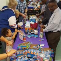 """Volunteers formed two assembly lines to package """"snack packs"""" for school children of Teaneck. JAMES PORTER PHOTO"""