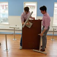 Chris Whitaker and Christopher Jennings assemble tables in the new classroom. NINA NICHOLSON PHOTO