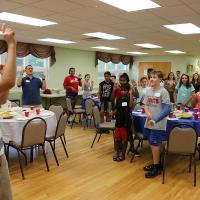 "Youth Fellow Matt Porowski leads the group in singing the ""Spiderman"" grace."