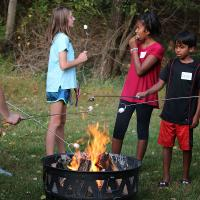 Toasting marshmallows and eating s'mores.