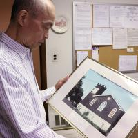 Gary Eng looks at a photo of the original St. Paul's building, built in 1914 and destroyed by fire in 1978. NINA NICHOLSON PHOTO