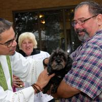 The Rev. Gregory Perez blesses pets at Trinity, Bayonne. PHIL BENSON PHOTO