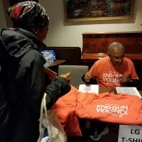 WASHINGTON: At 5:30 AM, Canon Greg Jacobs hands out T-shirts to bus riders at Episcopal House in Newark. NINA NICHOLSON PHOTO