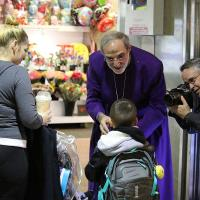 A Star-Ledger photographer photographs Bishop Mark Beckwith giving Ashes to Go to a family in Newark Penn Station. NINA NICHOLSON PHOTO