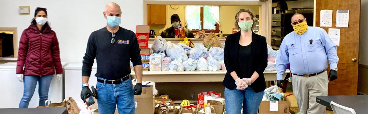 The Rev. Rod Perez-Vega (right) accepts a donation of food from a State Senate candidate, who ran a food drive as part of her campaign. PHOTO SOURCE: FACEBOOK