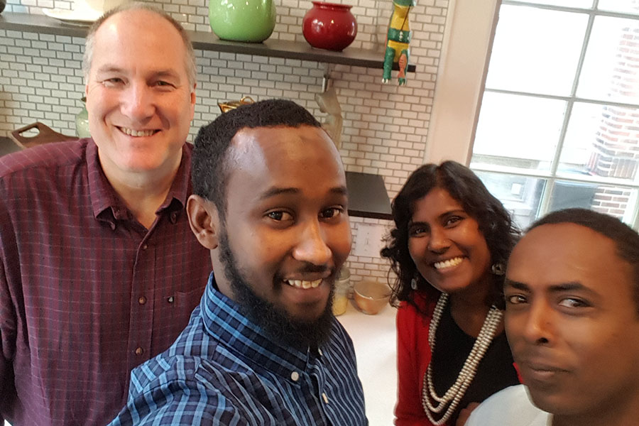 The Rev. Bernie Poppe in the kitchen of St. George's Rectory with (l-r) Jama, Sally Pillay (First Friends Program Director) and Paulos.
