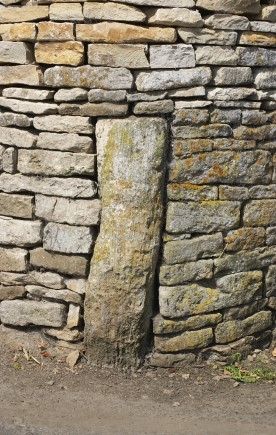 A roughhewn stone wall, featuring a cornerstone.